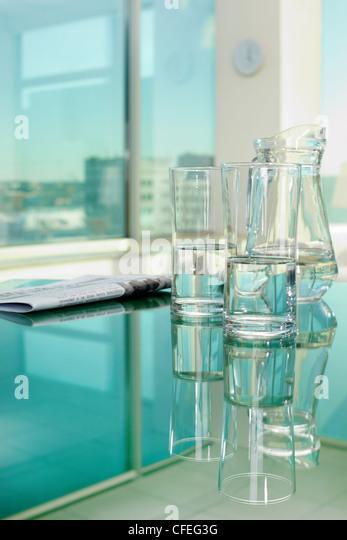 Nahaufnahme von Glaswaren und Zeitung auf Tisch Stockbild