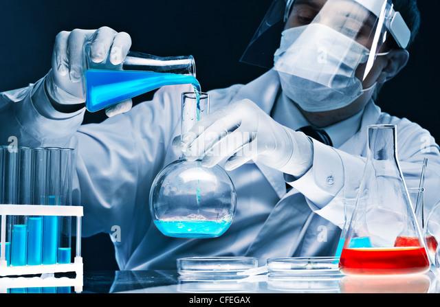Maskierte männliche Wissenschaftler mischen hell blaue Stoffe in Glaswaren Stockbild
