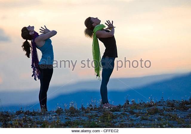 Zwei Frauen führen Hatha Yoga-Posen auf einem Berggipfel. Stockbild