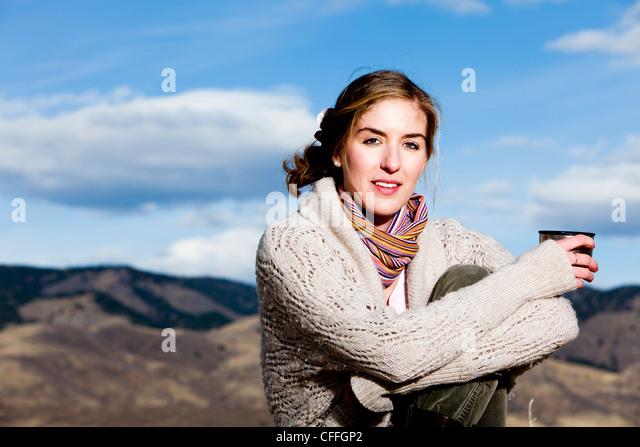 Eine junge Frau Kaffee nippt und posiert in geschichteten Outdoorbekleidung in Fort Collins, Colorado. Stockbild