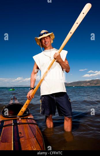 Ein Mann trägt ein Strohhut wie er posiert für ein Portrait mit einem Holz-Kajak und Paddel, das er im Stockbild