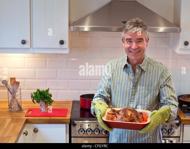 Lächeln auf den Lippen entspannt zuversichtlich, dass ältere Menschen in modernen Küche ein heißes Stockbild