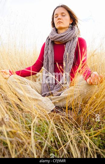 Schöne junge Frau in langen Wiese meditieren Stockbild