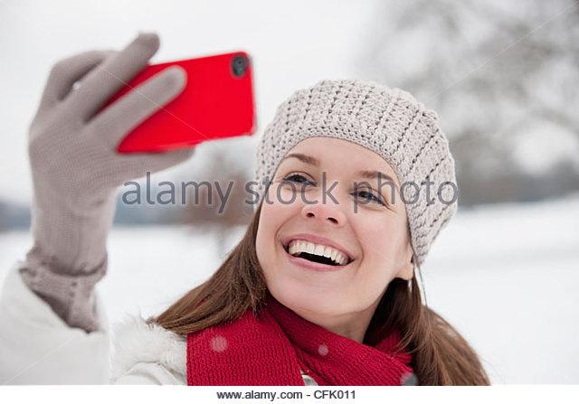 Eine junge Frau, wobei ein Foto von sich selbst im Schnee Stockbild