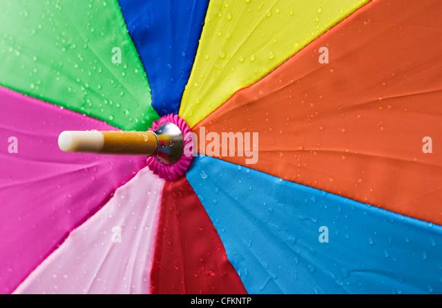 Nahaufnahme von einem bunten Schirm im Regen. Stockbild
