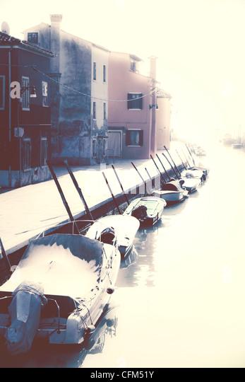 Boote in der Sonne auf einem Kanal in Burano, Venedig, Italien Stockbild
