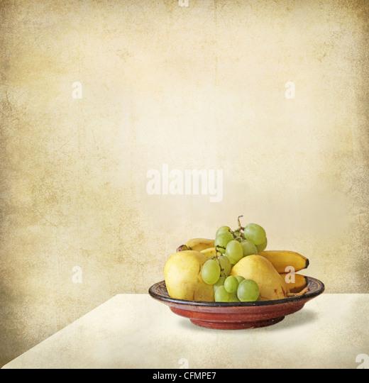 Grunge Stillleben mit einem hellen Interieur, ein Tisch und ein Tablett voller Früchte, Trauben, Bananen, Birnen. Stockbild