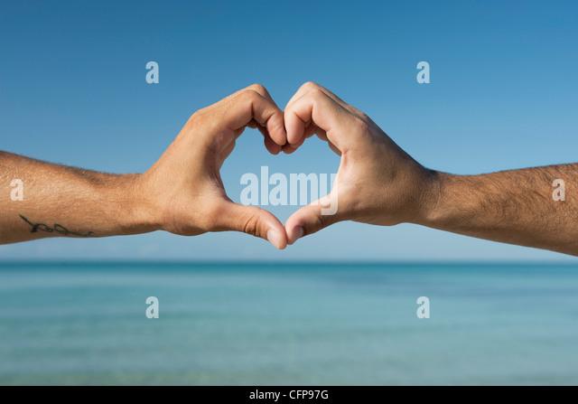 Zwei Männerhände bilden Herzform vom Ozean, beschnitten Stockbild