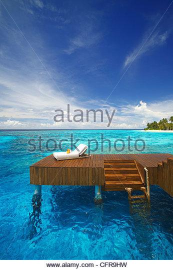 Sonnenliege und Steg in der blauen Lagune auf der tropischen Insel, Malediven, Indischer Ozean, Asien Stockbild