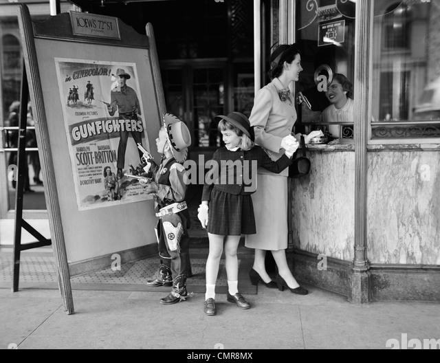 1950ER JAHREN MUTTER 2 KINDER KAUF VON TICKETS ZU FILM-MATINEE JUNGE TRAGEN COWBOY KOSTÜM Stockbild