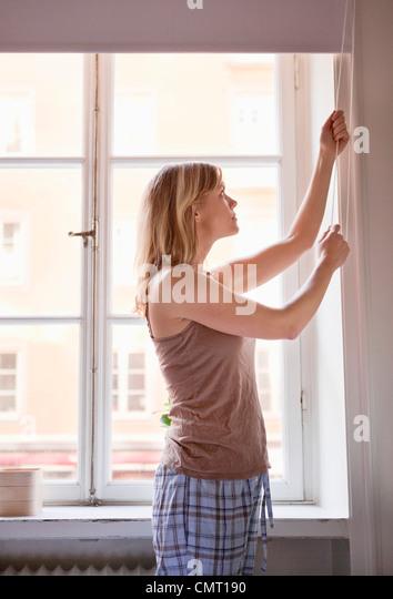 Frau steht vor einem Fenster ziehen einen blind Stockbild