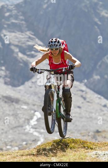 Frankreich, Dauphine, Vaujany, weibliche Mountainbiker springen Stockbild