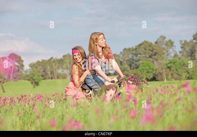 glückliche Mädchen Reiten Fahrrad oder mit dem Fahrrad im Sommerwiese Stockbild