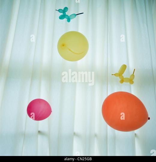 Bunte Luftballons gegen weißen Vorhang Stockbild