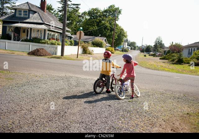 Bruder und Schwester auf Fahrrädern in Nachbarschaft Stockbild