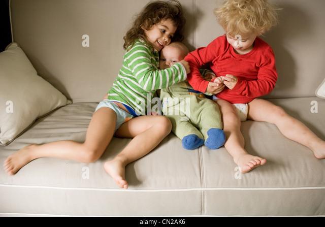 Drei Geschwister auf sofa Stockbild