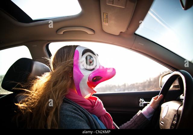 Frau Auto mit Clownsmaske Stockbild