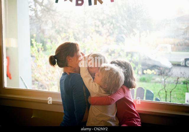 Mutter, drei Kinder umarmen Stockbild