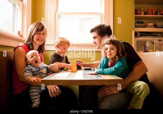 Familie sitzt am Küchentisch Stockbild