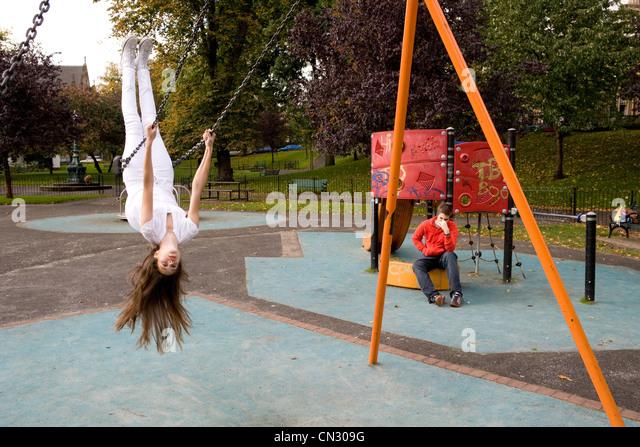 Teenager-Mädchen auf Schaukel Spielplatz, auf dem Kopf stehend Stockbild