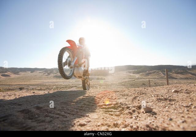 Mann tut Wheelie auf Dirt Bike auf Feldweg Stockbild