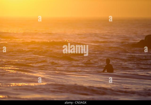 Surfer im Meer bei Sonnenuntergang Stockbild