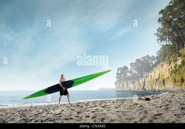 Surfer mit Surfbrett an Strand, Santa Cruz, Kalifornien, USA Stockbild