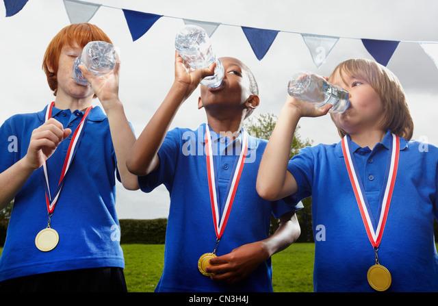 Schule Jungs mit Medaillen Trinkwasser nach Sport-event Stockbild