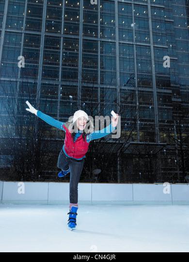 Frau, die ein Foto von sich beim Eislaufen Stockbild