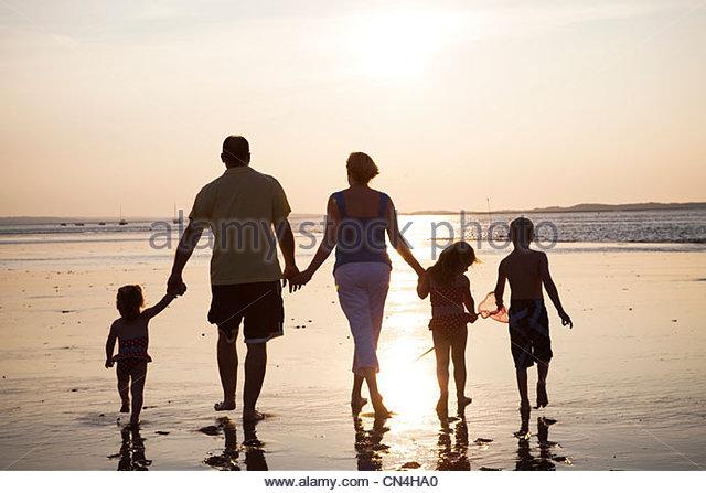 Fünfköpfige Familie zu Fuß am Strand bei Sonnenuntergang Stockbild