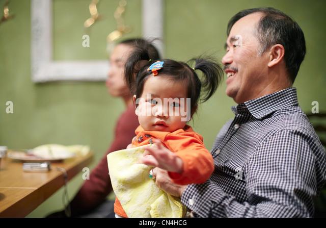 Kleinkind und Großvater am Thanksgiving-dinner Stockbild