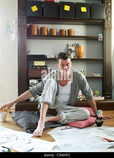 Mitte erwachsenen Mannes Blick auf Skizzen und Kunstwerke im Stock Stockbild