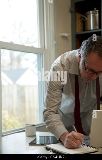 Reifer Mann Notizen zu Hause Stockbild