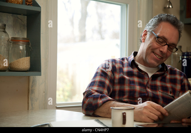 Reifer Mann zu Hause Magazin lesen Stockbild