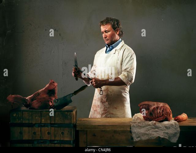 Metzgerei mit Fleisch vom Schwein, Messer schärfen Stockbild