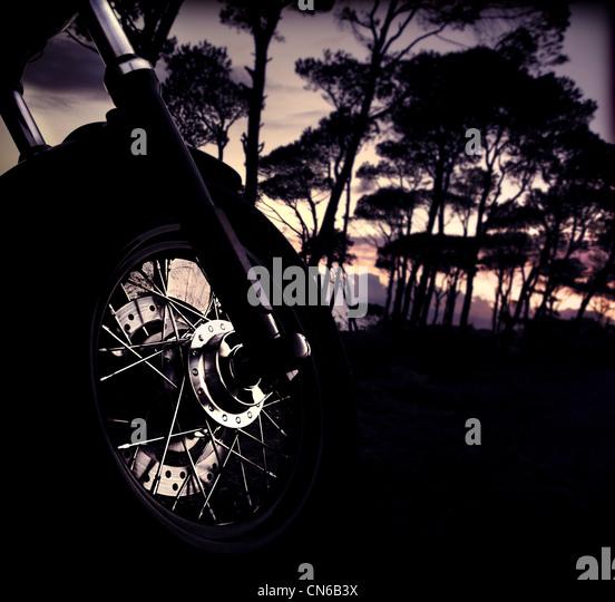 Motorrad-Rad über Wald Sonnenuntergang, selektiven Fokus auf Fahrrad, glänzende Reifen Details, outdoor Stockbild