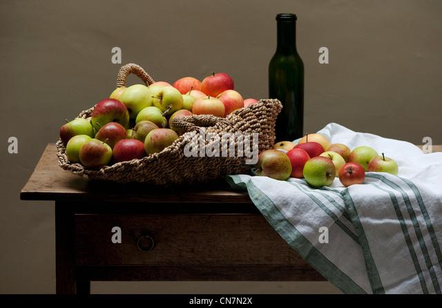 Korb mit Äpfeln und Wein auf Tisch Stockbild
