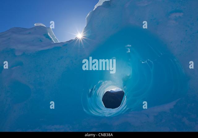 Kleine Tunnel in einem Eisberg eingefroren in Mendenhall Lake, Juneau, südöstlichen Alaska Winter erodiert Stockbild