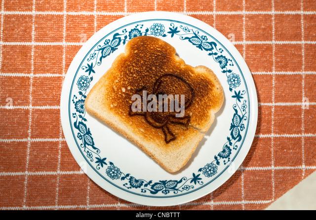 Schädel und gekreuzte Knochen in ein Stück Toast auf einer Platte verbrannt. Zöliakie Gluten Allergie Stockbild