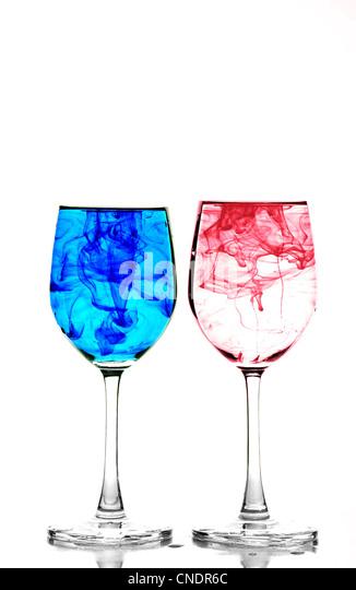 Zwei Gläser Wein mit Wasser gefüllt und Verbreitung rote und blaue Tinte Stockbild