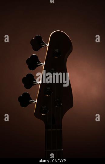Silhouette eines Bass-Gitarre-Kopfes auf braun Stockbild