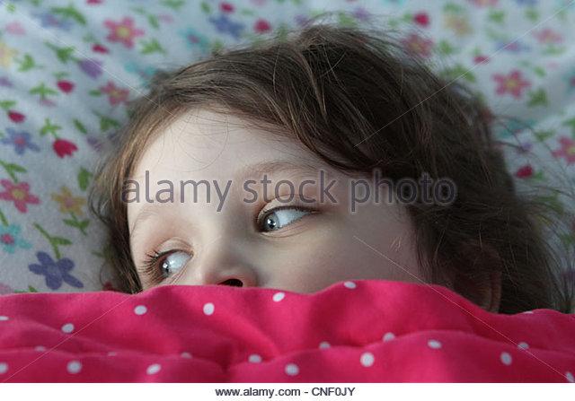 Ein kleines Kind im Bett mit decken bis zu Augen gezogen. Stockbild