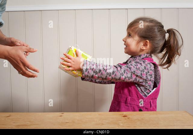 Kleines Mädchen geben ein Geschenk für Erwachsene Stockbild