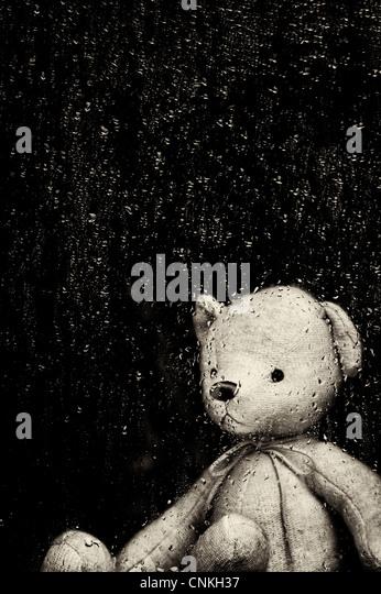 Traurig Teddybär Blick durch ein Fenster in Regentropfen fallen. Sepia getönt Stockbild