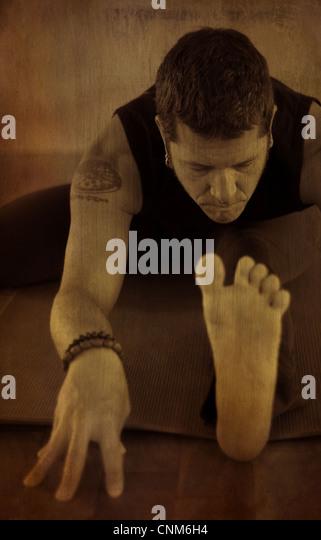 Ein Mann geht in ein sitzen nach vorne beugen Yoga zu praktizieren; eine Version des Janusirsasana. Foto mit Textur Stockbild