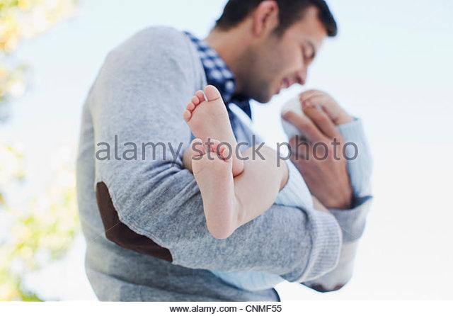 Vater Holding Baby im freien Stockbild
