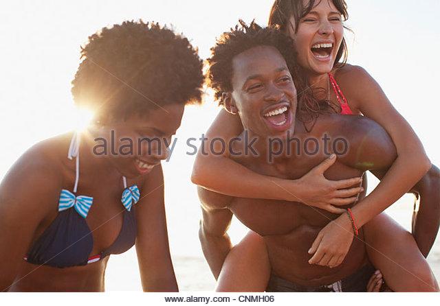 Freunde spielen gemeinsam am Strand Stockbild