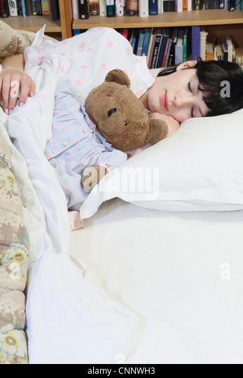 Frau umarmt Teddybär im Bett Stockbild