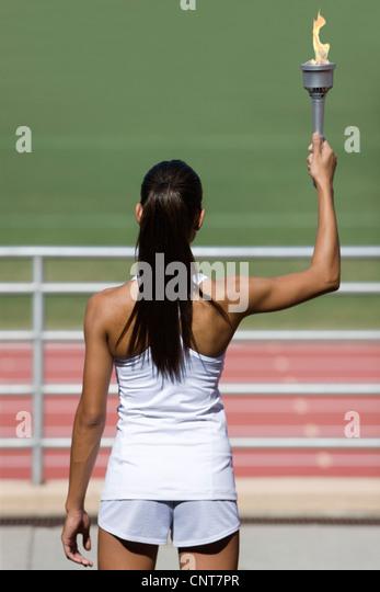 Sportlerin, hält Fackel, Rückansicht Stockbild