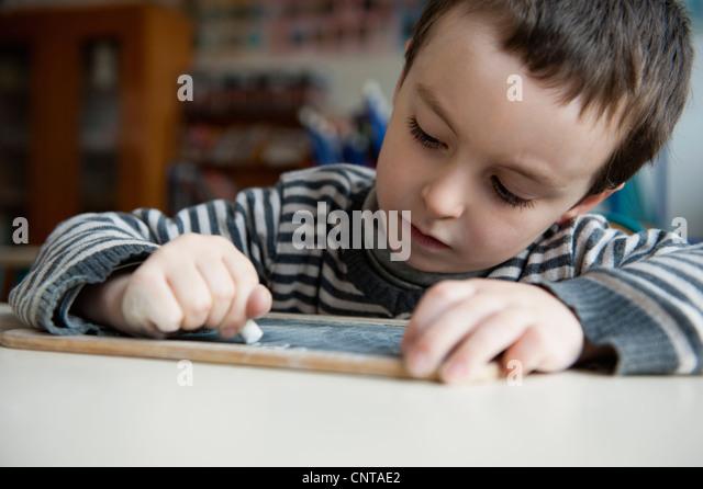 Junge an Tafel schreiben Stockbild